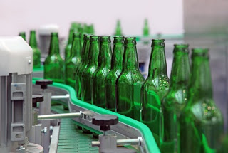 Empty green beer bottles on conveyor belt ready to be filled