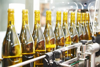 Filled wine bottles moving along a conveyor belt