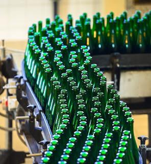 Green bottles moving along a conveyor belt system